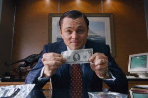 leonardo di caprio tiene in mano una banconota da un dollaro nel film the wolf of wall street